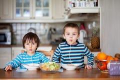 Två söta barn, pojkebröder och att ha för lunchspagetti på arkivfoton