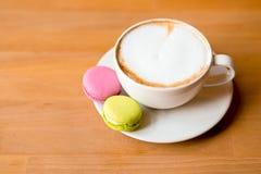 Två söta makron och en kopp av cappuccino arkivbild