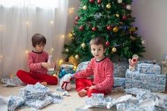 Två söta pojkar, öppnande gåvor på juldag Arkivfoto