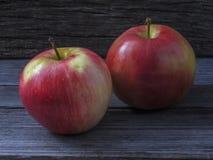 Två saftiga mogna röd-guling äpplen på en trätabell fotografering för bildbyråer