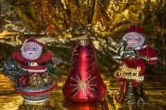 Två Santa Claus och en julklocka, på en guld- bakgrund arkivbild