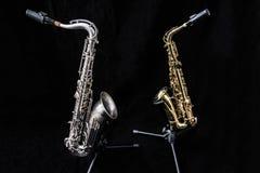 Två saxofoner som står isolerade i svart royaltyfria bilder