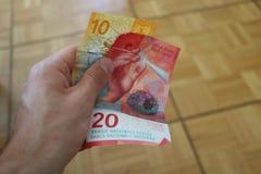 Två schweizisk franc sedel i en manhand royaltyfri foto