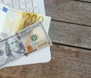 Två sedlar av dollar och euro som ligger på en bärbar dator och en trätabell Royaltyfria Bilder