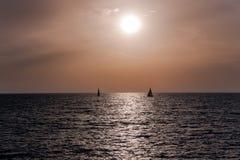 Två segelbåtar på solnedgången i orange signaler arkivfoto