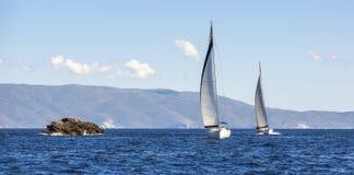 Två segelbåtar seglar eller seglar regattaloppet på havet för blått vatten sport Fotografering för Bildbyråer