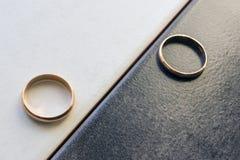 Två separata vigselringar på en svartvit bakgrund Conc Fotografering för Bildbyråer