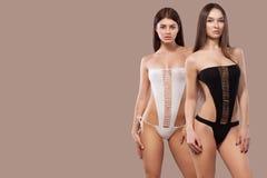 Två sexiga brunettkvinnor som bär svartvit swimwear som poserar på brun bakgrund perfekt huvuddel Bikinisommar Fotografering för Bildbyråer