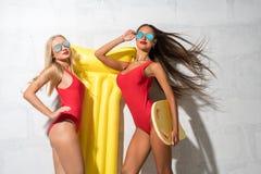 Två sexiga flickor med den gula luftmadrassen nära den soliga väggen Fotografering för Bildbyråer