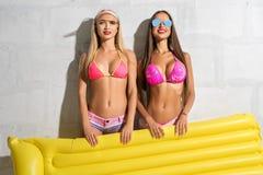 Två sexiga flickor med simningluftmadrassen Arkivfoton