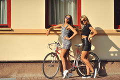 Två sexiga flickor nära en tappningcykel Royaltyfri Fotografi