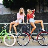 Två sexiga flickor på cyklar i en sommartid - utomhus- mode p Arkivfoto
