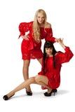 Två sexiga kvinnor i coctailklänning. fotografering för bildbyråer