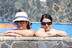 Två sexiga kvinnor i pölen Fokus i den högra damen Royaltyfri Fotografi