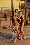 Två sexiga kvinnor med tappningcykeln utomhus- stående för mode Fotografering för Bildbyråer