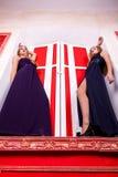 Två sexiga kvinnor på fönsterbräda i rik tappninginre royaltyfri fotografi