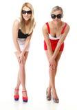 Två sexiga kvinnor som bär kortkortkjolar Arkivfoton