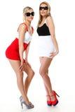 Två sexiga kvinnor som bär kortkortkjolar Fotografering för Bildbyråer