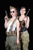 Två sexiga kvinnor som poserar den militära likformign WW2 och vapen Royaltyfri Foto