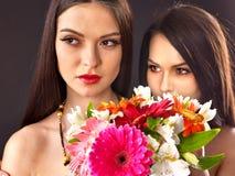 Två sexiga lesbiska kvinnor med blomman. Arkivfoton