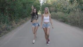Två sexiga varma kvinnor som tillsammans går längs vägen på skogen eller, parkerar Blondin och brunett som promenerar vägen stead stock video