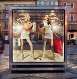 Två shoppa kvinnor på utställningfönster Royaltyfri Bild