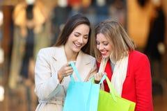 Två shoppare som visar produkter i shoppingpåsar royaltyfri bild