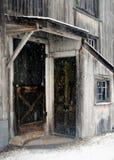 Två sidodörr och multipelfönster till den gamla smutsiga vita New England ladugården i en December snöstorm Royaltyfri Bild