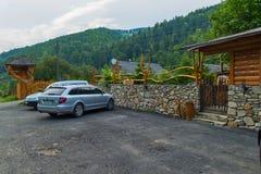 Två silverbilar i en mycket liten parkeringsplats med ett vide- staket nära ett kafé i ett huggit av hus arkivfoto