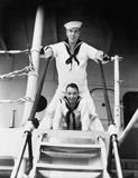 Två sjömän som står på en landgång (alla visade personer inte är längre uppehälle, och inget gods finns Leverantörgarantier som t royaltyfri fotografi