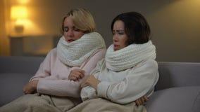 Två sjuka flickor som sitter med halsdukar i säng och nyser, influensavirus, hälsovård lager videofilmer