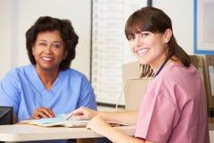 Två sjuksköterskor i diskussion på sjuksköterskor posterar Arkivfoto