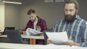 Två skäggiga kontorsarbetare arbetar i kontoret som studerar den anmäla dokumentationen Kollegor läste legitimationshandlingar me stock video