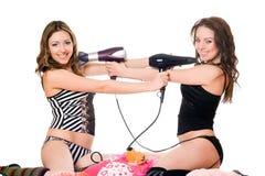 Två skämtsamma flickvänner med hårtorkar. Isolerat Fotografering för Bildbyråer