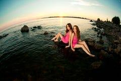 Två skönhetkvinnor på stranden på solnedgången. Tyck om naturen. Lyxig gi Arkivfoto