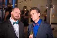Två skeptiska mogna män på ett parti arkivbilder