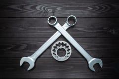 Två skiftnycklar och kugghjul på mörk träbakgrund royaltyfri foto