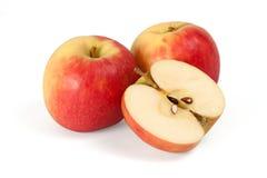 Två skivade äpplen och half äpple Arkivfoto