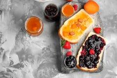 Två skivor av bröd med aprikos- och bärdriftstopp royaltyfri fotografi