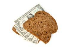 Två skivor av bröd som överträffas med kontanta dollarräkningar Royaltyfri Fotografi