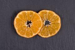 Två skivor av mandarin ligger på svart kritiserar Begrepp av sunt som är organiskt, strikt vegetarianmat, vitaminer Top beskådar  royaltyfri foto
