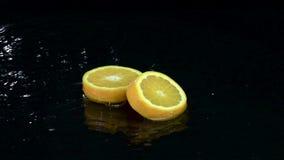 Två skivor av orangefall in i vattnet Svart bakgrund långsam rörelse lager videofilmer