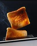 Två skivor av rostat bröd i en brödrost Arkivfoton