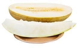 Två skivor och halva av denryss melon på plattan Royaltyfria Foton
