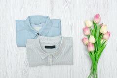 Två skjortor och en bukett av tulpan trendigt begrepp Assortm Arkivfoto