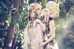 Två skognymfer som weraing utsmyckade hattar Fotografering för Bildbyråer