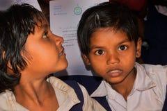Två skolaflickor från en lantlig grundskola för barn mellan 5 och 11 år av Bengal, såg in mot kameralinsen arkivbild