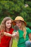 Två skolaflickor som undersöker naturen arkivfoton
