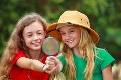 Två skolaflickor som undersöker naturen arkivfoto