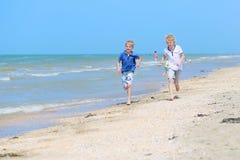 Två skolapojkar som kör på stranden Royaltyfria Foton